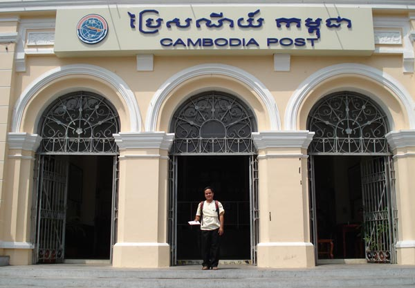 A photo of a man standing outside a Cambodian Post Office